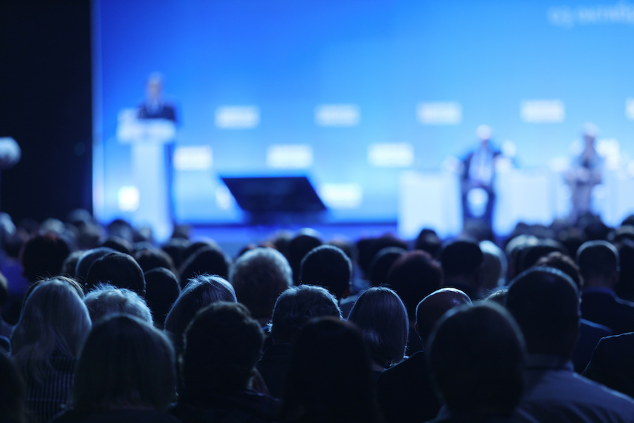 Speaker announcing product to a large crowd during a conference.