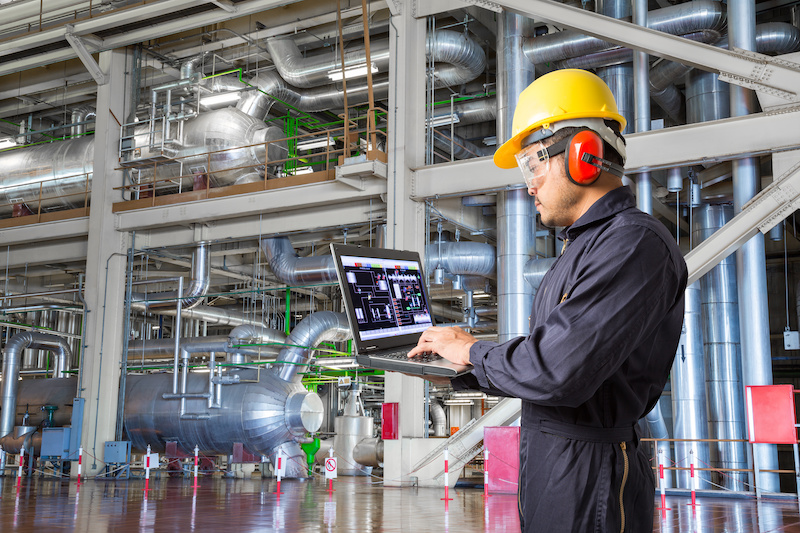 Engineer using laptop computer for maintenance.