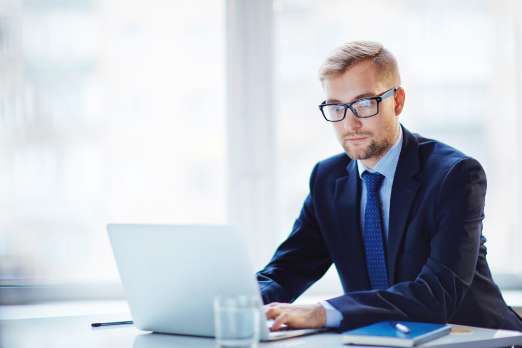 Adult Male Wearing Suit and Tie Working on Laptop in White Room