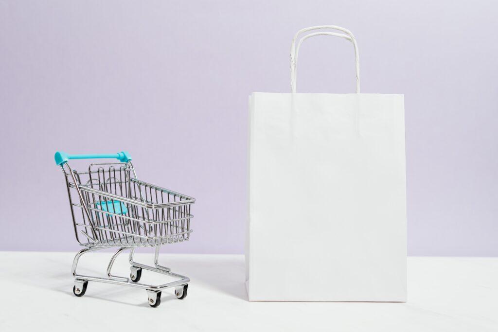 Shopping cart beside a shopping bag.