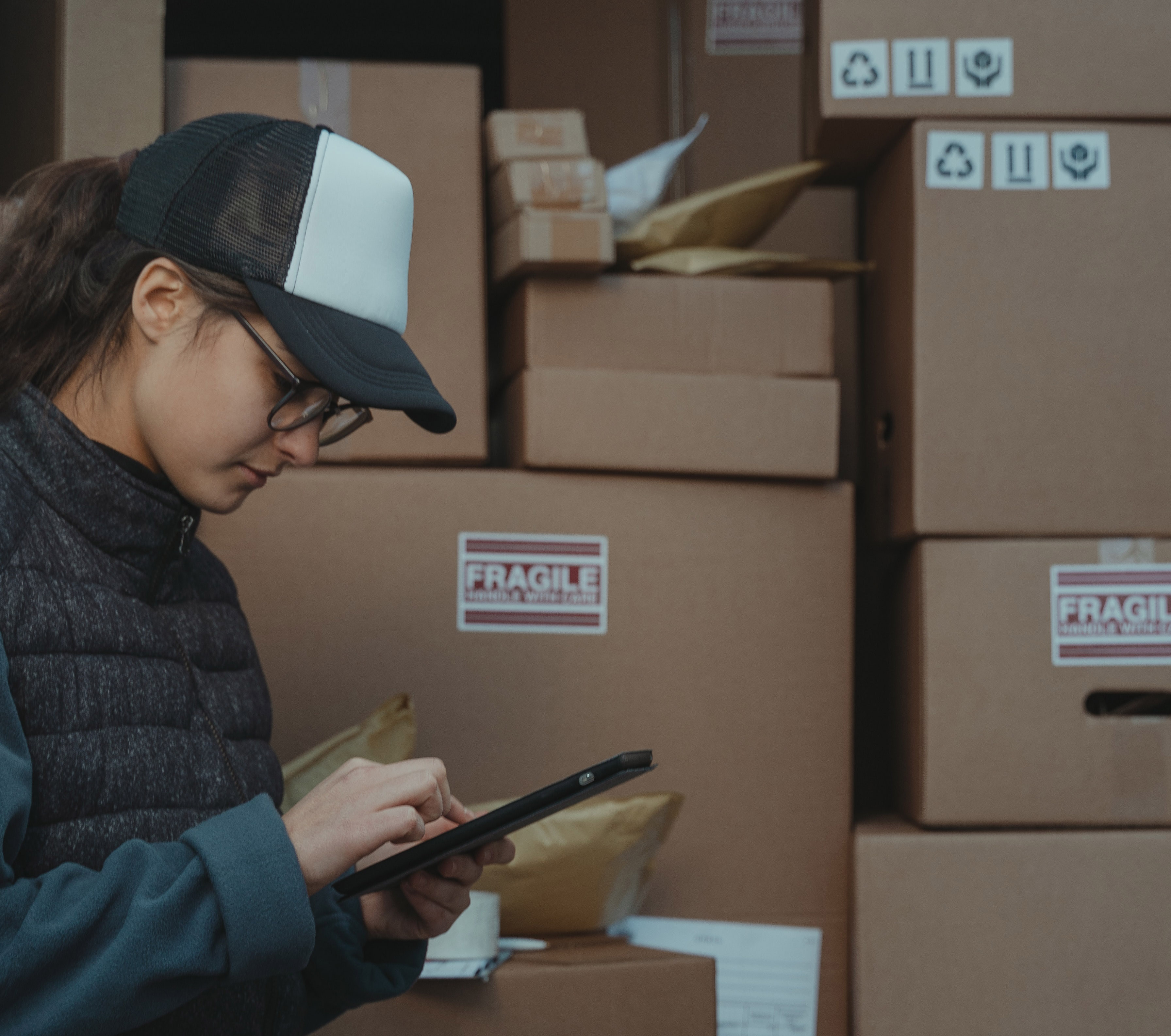 Woman checking device with delivery boxes behind her.