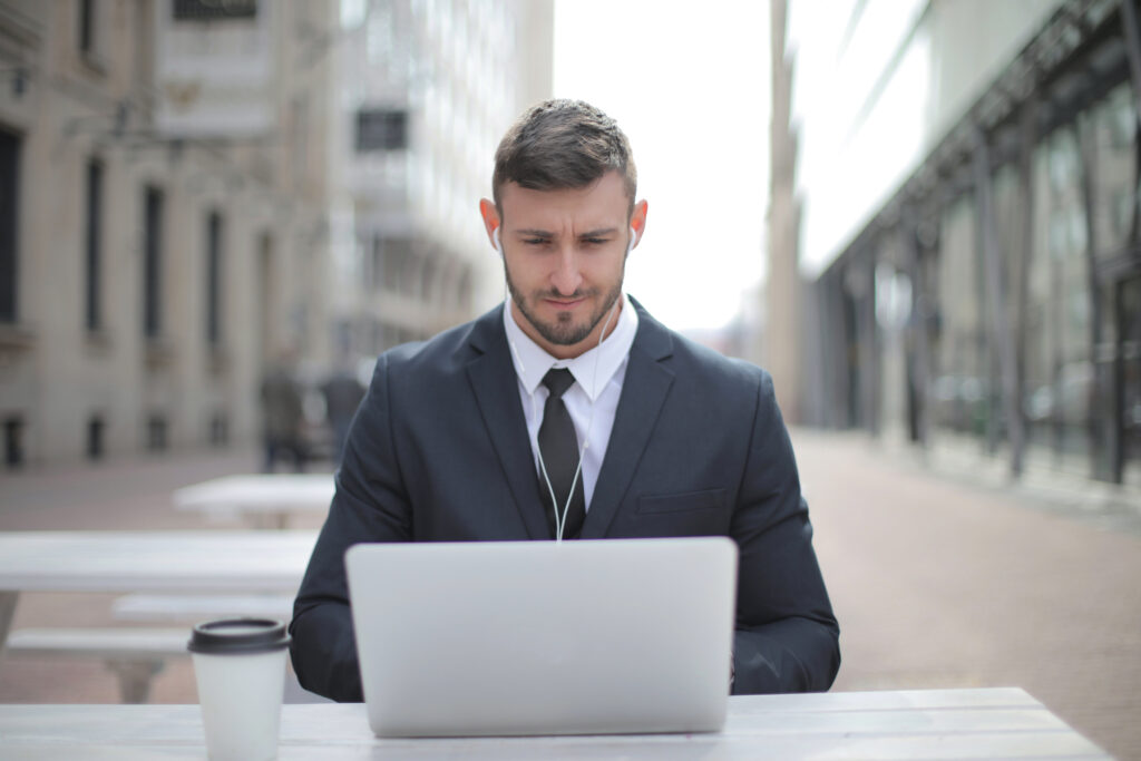 Man in business suit working on a laptop outdoors.